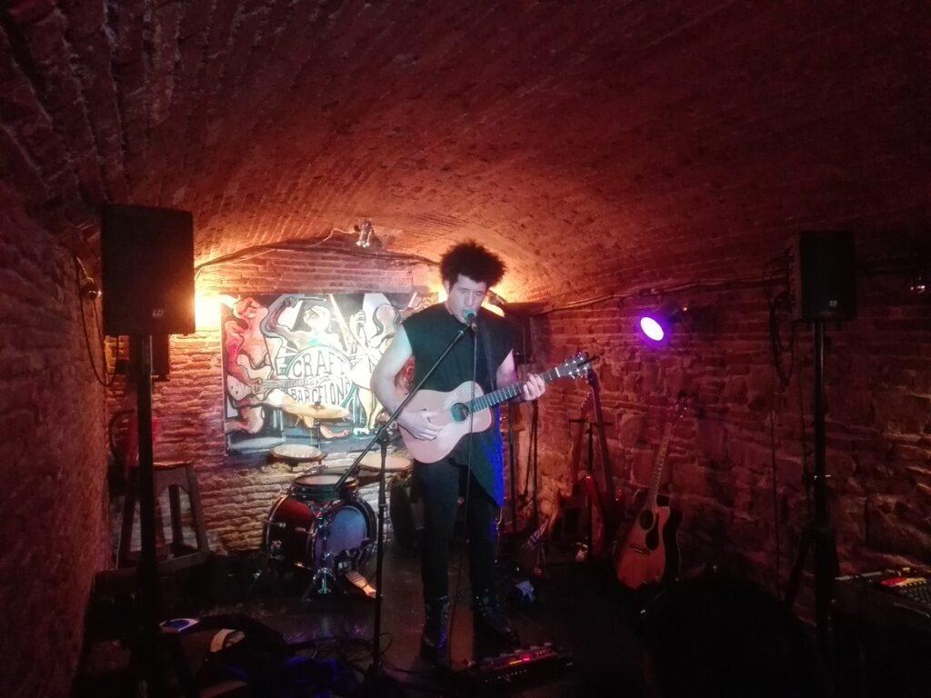Chanteur expressif avec sa guitare au Craft à Barcelone