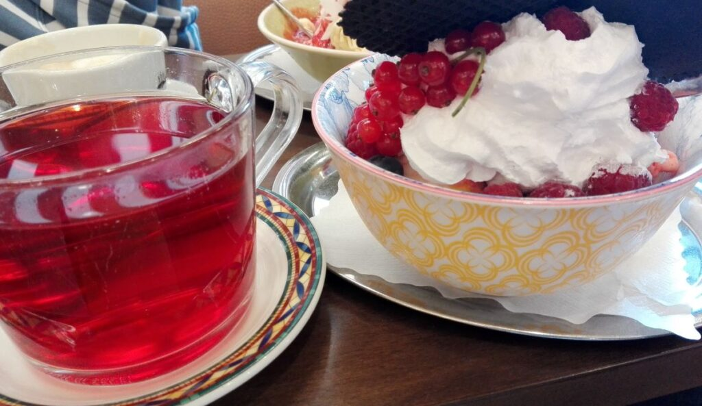 Red berry herbal tea and cup of forest berries and vegan ice cream